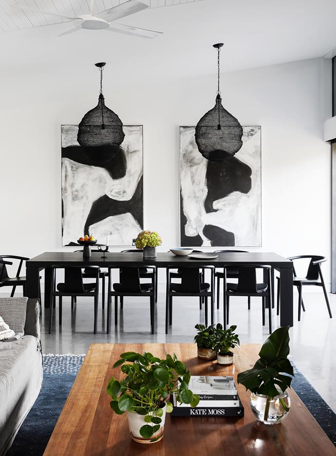 Family meals take place at the Zuster dining table, surrounded by Kiki dining chairs from MCM House. Brickett Davda ceramic plate and bowl and Henry Dean square grey glass vase, all from Manon Bis. Artworks by Kate Scott through LuMu Interiors.  Smart buy: Luca pendant lights, from $295 each, LuMu Interiors.