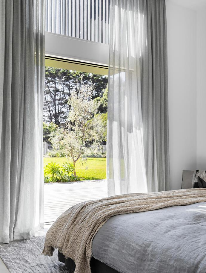Curtains from Clearview Sun Control soften the sunny view out to the garden. The bed from MCM House is draped with a Hale Mercantile Co 'Sable' blanket. Rug, Loom Rugs.