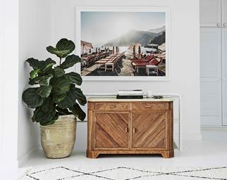 Photographic art hanging above a timber sideboard