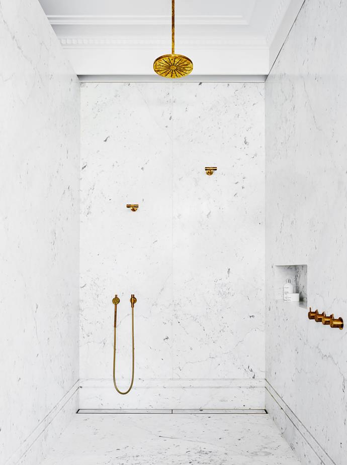 Wall finish Bianco Carrara marble from CDK Stone. Showerhead/tapware Vola ceiling-mounted shower and hand shower in Raw Brass finish.