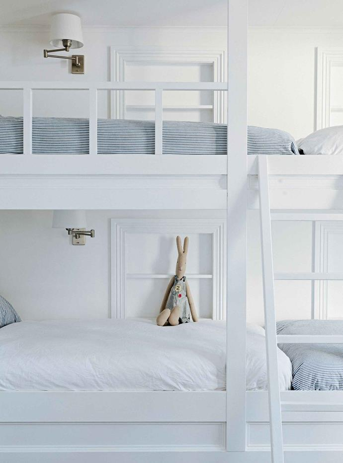 **CLEAN AND SERENE**<p> <p>Bunk beds are great space savers, and a calming all-white colour schene will make a small room feel spacious and calming. Here, linen in blue ticking fabric add subdued colour while extendable wall lamps add another layer of functionality. <p>