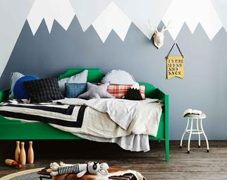 Kids bedroom with green bed and mountain wall mural