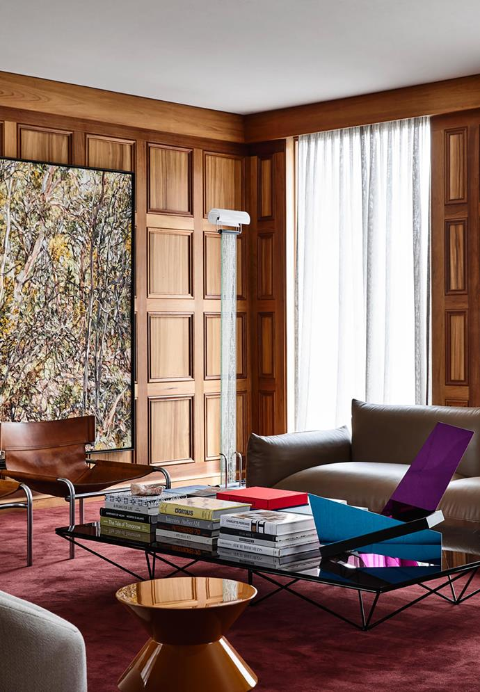 Wilpena wattle and scrub by Nicholas Harding from Sophie Gannon Gallery sits against original blackwood wall panelling in the family room. Vintage leather and steel chairs from Modern Times, vintage 1980s floor lamp, Arflex 'Marenco' sofa from Poliform and a Minotti 'Cesar' side table from De De Ce surround a B&B Italia 'Alanda' coffee table by Paolo Piva from Space. The table is stacked with art books and a John Nicholson sculpture from Sophie Gannon Gallery. Tisca 'Versailles' carpet in Kastanie from Halcyon Lake.