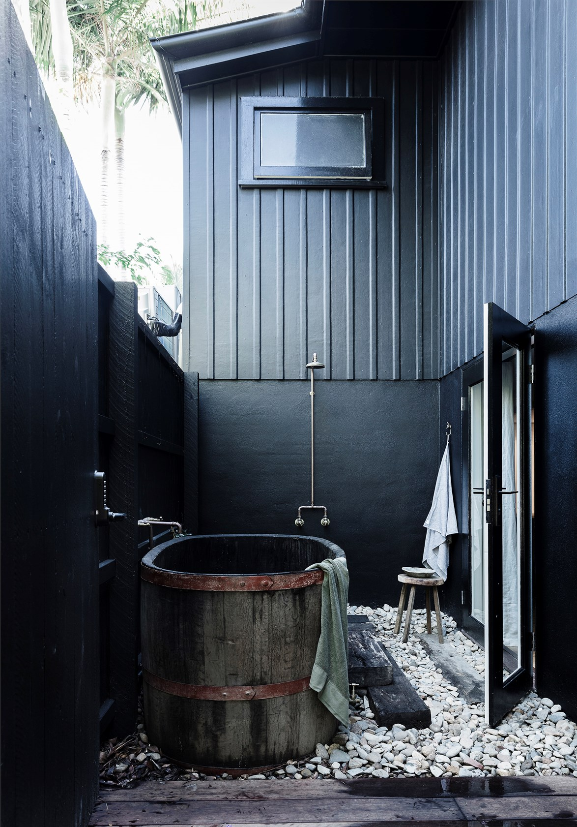 "Painting the exterior of this Byron Bay [beach house](https://www.homestolove.com.au/beach-house-decorating-ideas-13529|target=""_blank"") a dark colour accentuates its linear details and helps the home blend in with its tropical surrounds."