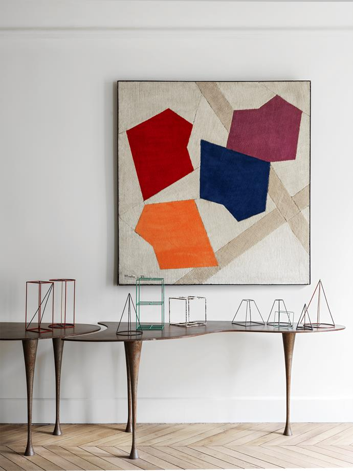 The only work on fabric by French painter René Roche hangs above a vintage console by Pucci de Rossi in this ultra-chic Parisian apartment reinvented by Jacques Hervouet.