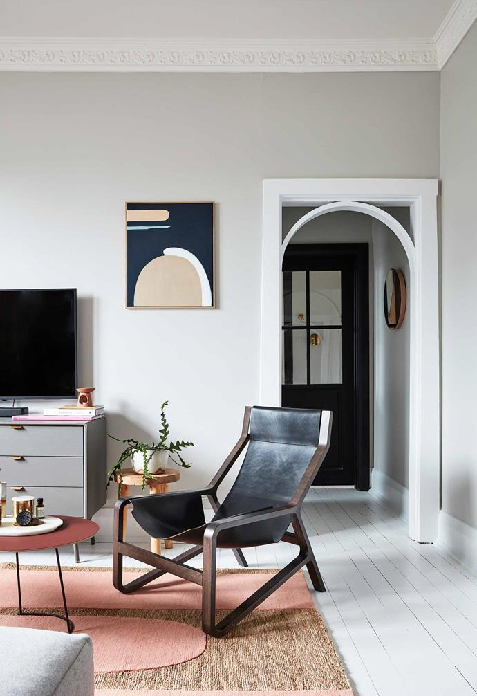 "White floorboards, white skirtings and soft grey walls provide a calm backdrop for the playful furnishings. Sophie added a bright white curved arch to the doorway leading to the bedroom and bathroom. Toro lounge chair in Night and Dang media stand, both from [Blu Dot](https://www.bludot.com.au/|target=""_blank""