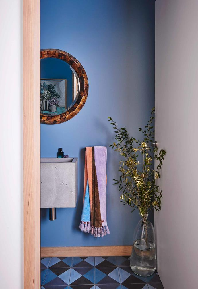 "A simple [concrete basin](https://www.homestolove.com.au/concrete-sink-trend-20300|target=""_blank"") is paired with a statement mirror and blue wall in the powder room of this colourful home."