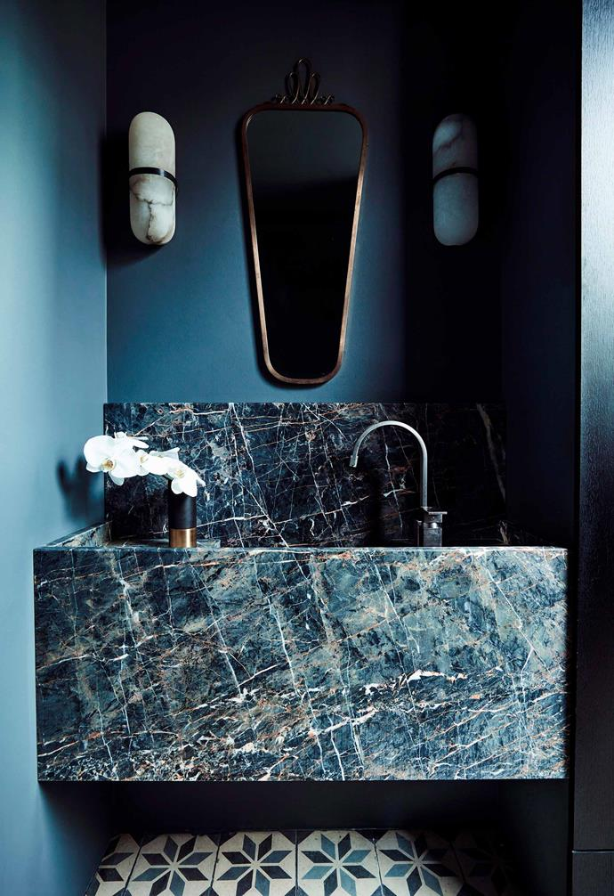 This statement powder room features striking marble paired with a patterned tile.