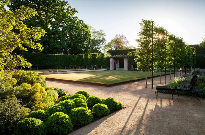 The central raised lawn area is flanked by pleached hedges of hornbeam, creating a sense of structure and enclosure within the space.