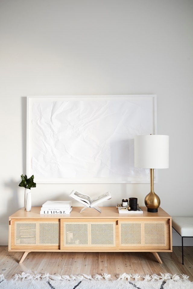 "This rattan sideboard from Ha'veli provides the perfect place for [homeowner Hayley Bonham](https://www.homestolove.com.au/hayley-bonham-home-20627|target=""_blank"") to practice her classic, restrained style using neutral tones and a touch of gold to glam things up."
