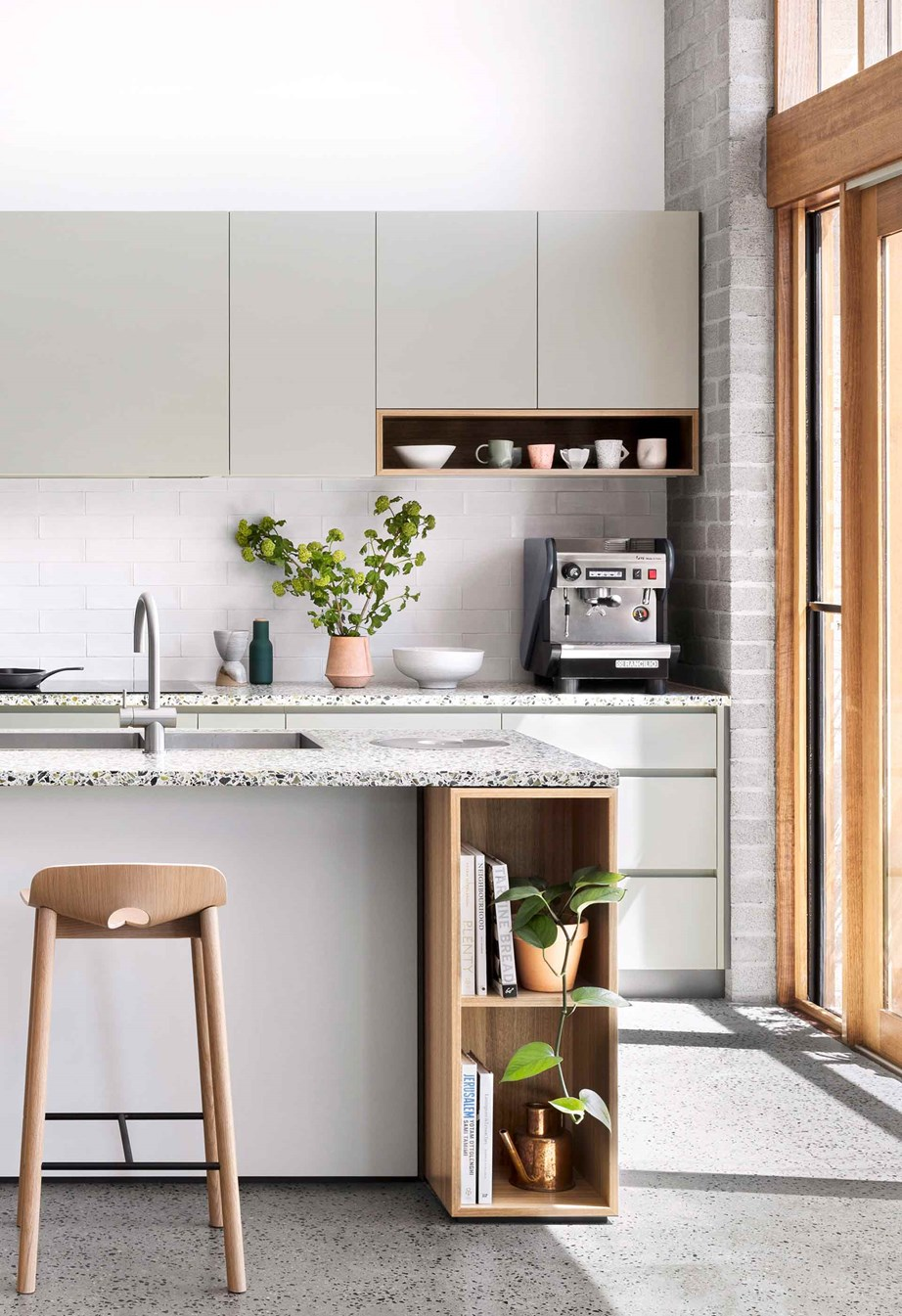 A custom shelf above this coffee machine allow easy access to cups while adding character to the kitchen.