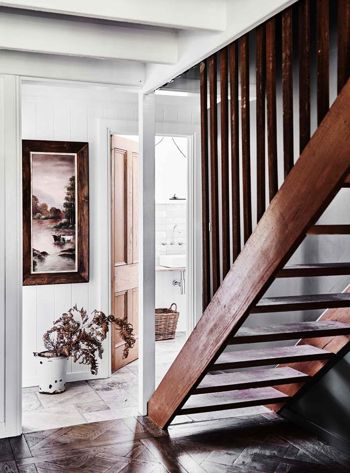 "A staircase leads to the guest bedroom. The framed vintage artwork is one of Danni's many collectables. Oak parquetry floors from [Schots Home Emporium](https://www.schots.com.au/|target=""_blank""