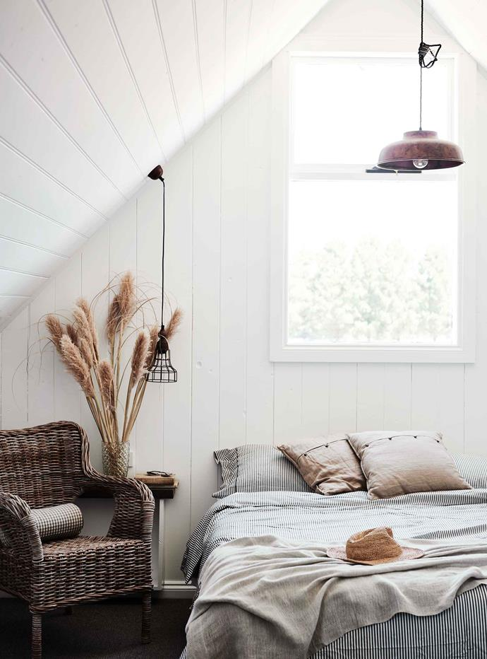 "The attic guest bedroom in the farmhouse has a rattan Byholma chair from [IKEA](https://fave.co/2N4J2RY|target=""_blank""