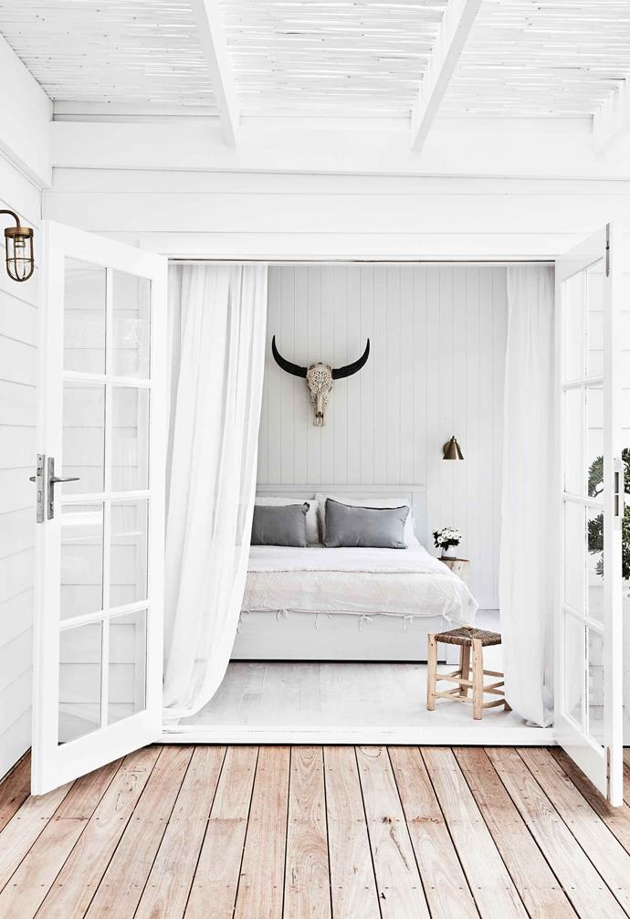 """**Guest bedroom** Framed by billowing sheers at French doors that open to the rear deck, this room delivers on the brief for tranquillity and contemporary luxury. """"We wanted this room to be really lovely for visiting family and friends,"""" says Natalie. On the wall above the bed, a carved cow skull from Indonesia adds drama. Stool, [The Pot Warehouse](http://www.thepotwarehouse.com/