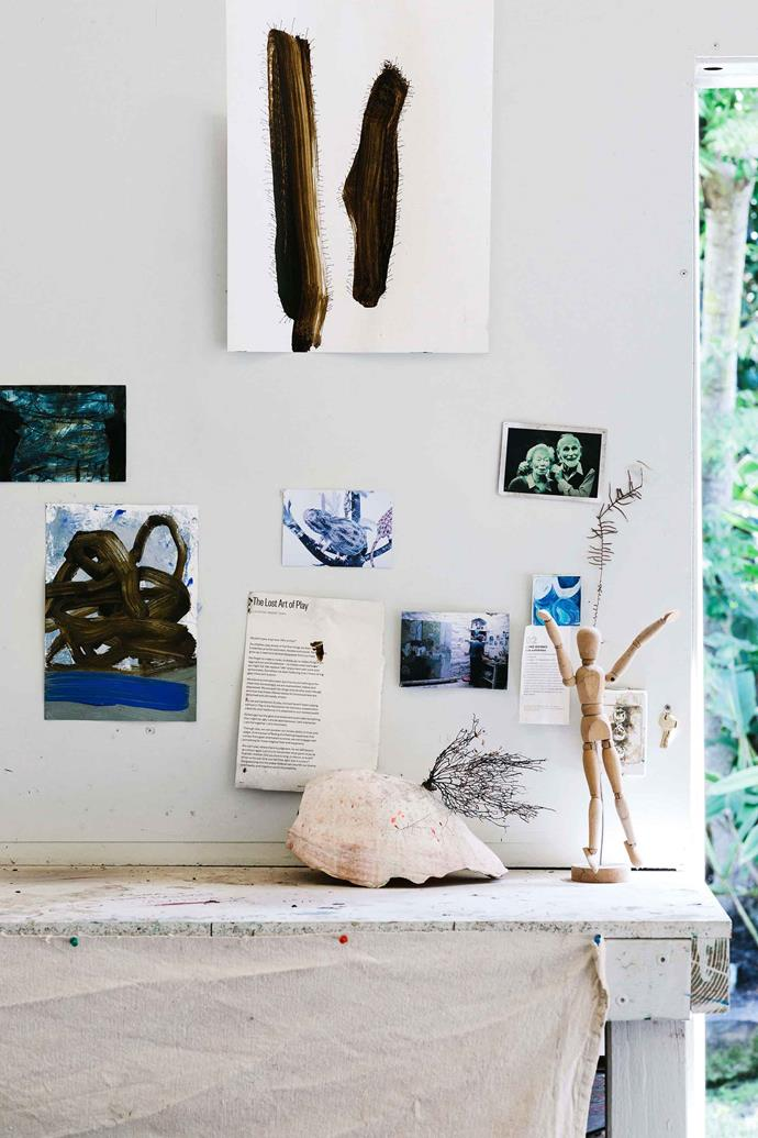 A wooden artist's manikin and foraged objects decorate the studio.