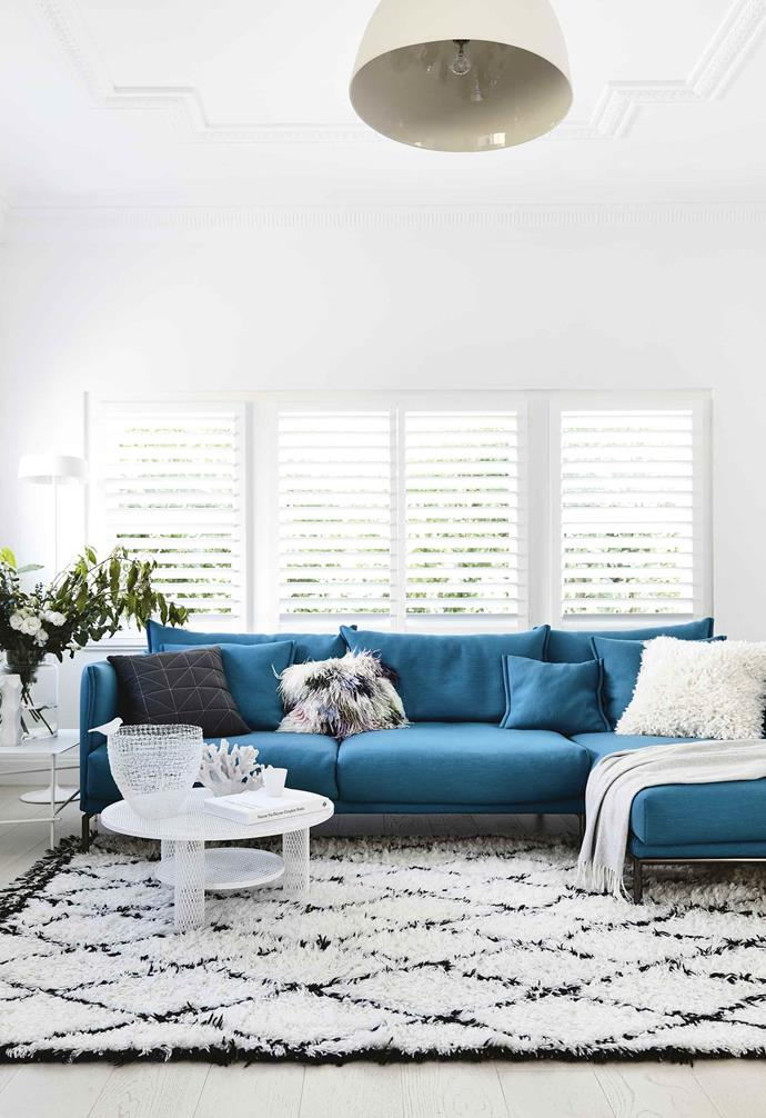 "This [minimalist all-white home](https://www.homestolove.com.au/how-to-add-bright-colour-to-a-minimalist-style-home-18410|target=""_blank"") features generous plantation shutters in the living room to allow for ample natural light, while blending seamlessly into the pared-back aesthetic.<br><br>"