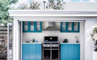 Weber barbecue in a blue outdoor kitchen