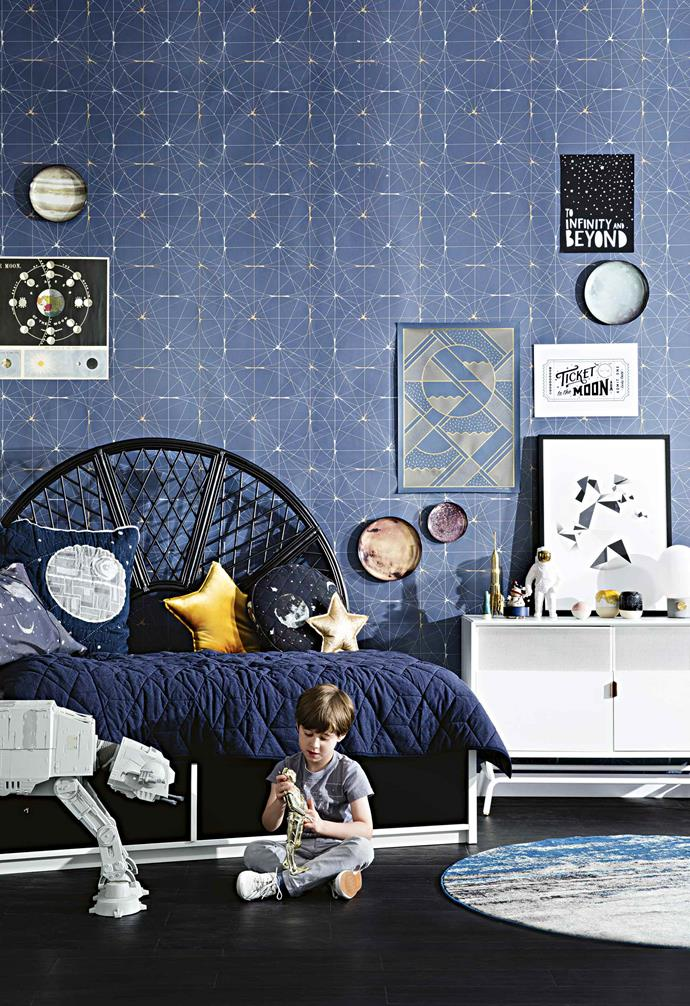 This Star Wars-inspired kids room features a patterned wallpaper that could easily pass as the night sky on first impressions. Astrology-themed cushions and art add a playful touch.
