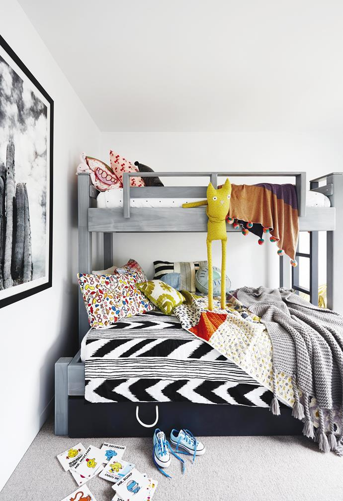 "In this kid's room of [this coastal holiday home](https://www.homestolove.com.au/coastal-holiday-home-19311|target=""_blank"") a bunk bed with stoway trundle is paired with colourful and patterned cushions and bedding for a playful contrast.<br><br>"