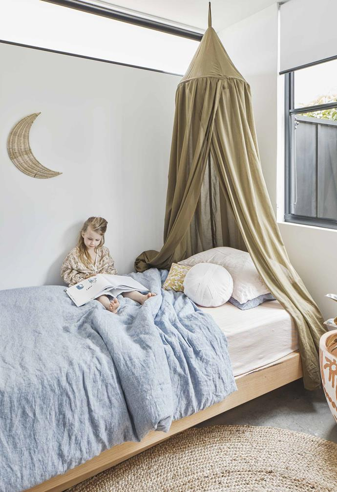 "A dreamy canopy over the bed is the central feature of the kid's room in this [Palm Springs-style Casuarina home](https://www.homestolove.com.au/palm-springs-inspired-home-19646|target=""_blank""). The neutral colour of the company complements the white and blue bedding as well as the timber bedframe, woven rug, and concrete flooring.<br><br>"