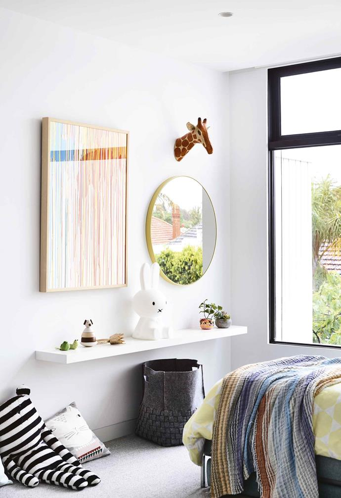 "Storage is king when it comes to creating a functional kid's room, whether it's under the bed, in the wardrobe, or with floating shelves. The floating shelf in the kid's room of this [minimalist period home](https://www.homestolove.com.au/minimalist-period-house-18410|target=""_blank"") is paired with a colourful artwork and mirror to create a playful vignette.<br><br>"