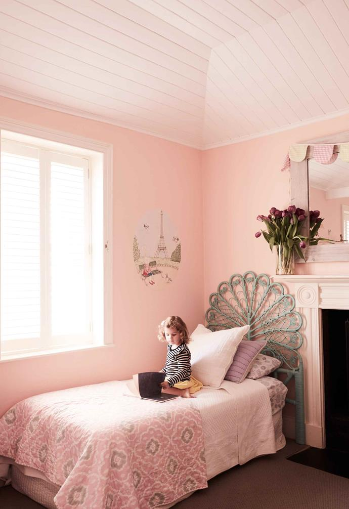 While this dreamy kid's room is light on statement pieces, painting the walls and ceiling panels in pink adds a soft and romantic ambience to the space. The sage cane bedhead is the perfect finishing touch.<br><br>