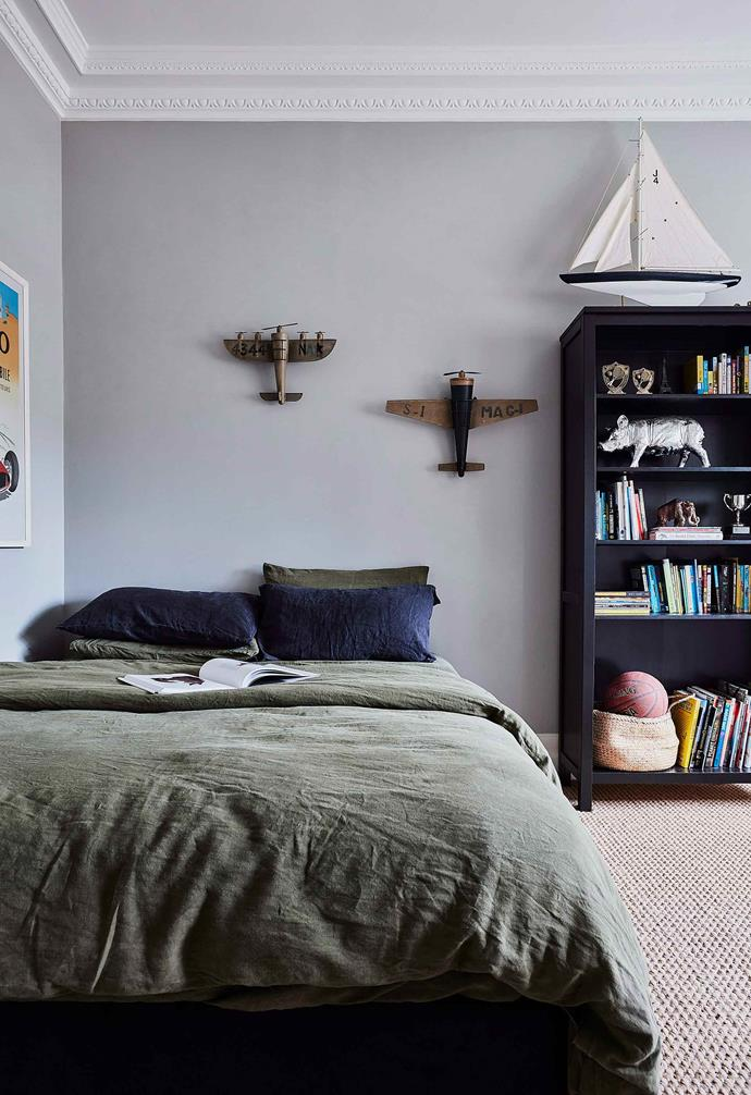 This kid's room takes a more pared-back approach to a traveller's theme. The rustic airplane models on the wall above the bed as well as the large-scale model of a yacht on the bookshelf add a playful touch.<br><br>