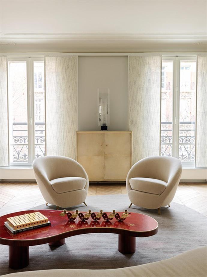 Armchairs designed by Federico Munari in the mid-1950s upholstered in Pierre Frey 'Teddy' fabric sit side-by-side in this Paris apartment by Jacques Hervouet. *Photograph: Stephan Julliard | Styling: Sarah De Beaumont.*