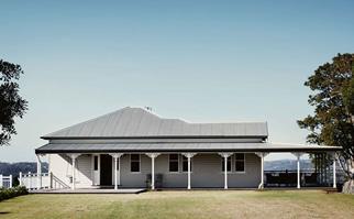 White weatherboard Queenslander house