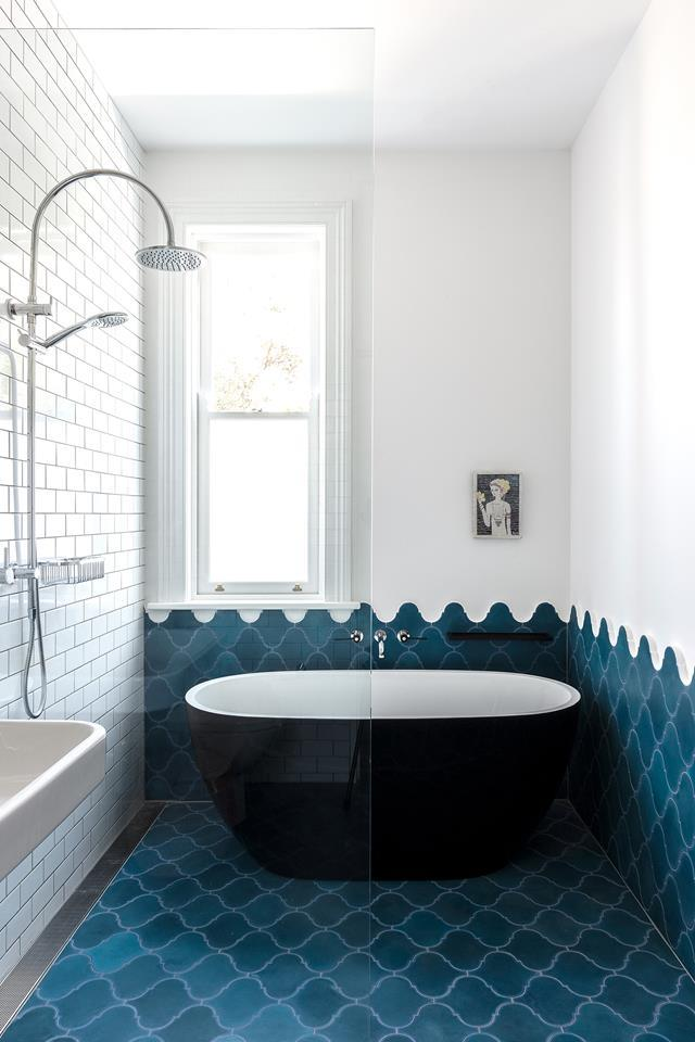 "Encaustic-cement tiles in cobalt blue from Terranova have been laid to to create a wave-like pattern in this [coastal inspired bathroom](https://www.homestolove.com.au/coastal-inspired-bathroom-19399|target=""_blank"")."