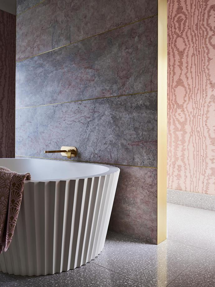 Purple Oniciata marble feature wall from Nefiko Marble. Bath Apaiser 'Origami' bath by Kelly Hoppen. Bath tapware Astra Walker 'Metropolis' in Urban Brass.