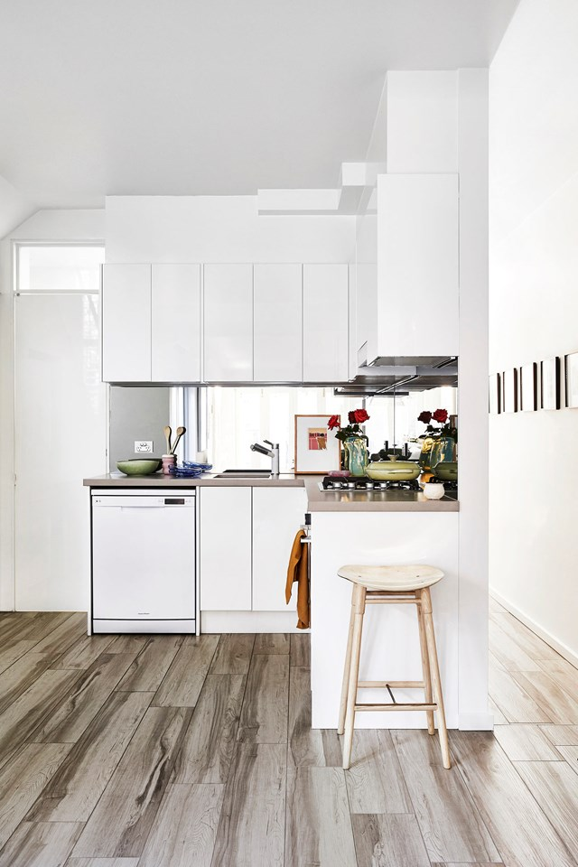 White walls and white cabinetry make this compact kitchen feel open and spacious.