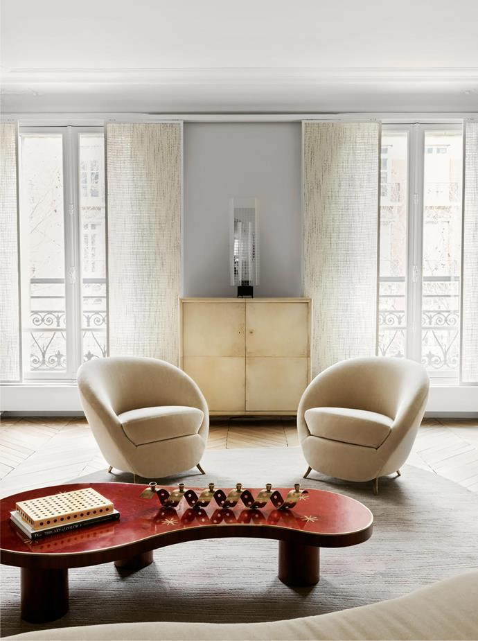 Armchairs designed by Federico Munari from the mid-1950s upholstered in Pierre Frey 'Teddy' fabric. A vintage Jean Royère 'Flaque' coffee table displays a metal Jean Royère candleholder from Galerie Jousse Entreprise. Jacques used sliding fabric panels as window treatments on account of his aversion to curtains. Between the two windows, a 1970s American skyscraper sculpture stands on an art deco cabinet in wood and parchment by Maison Dominique.