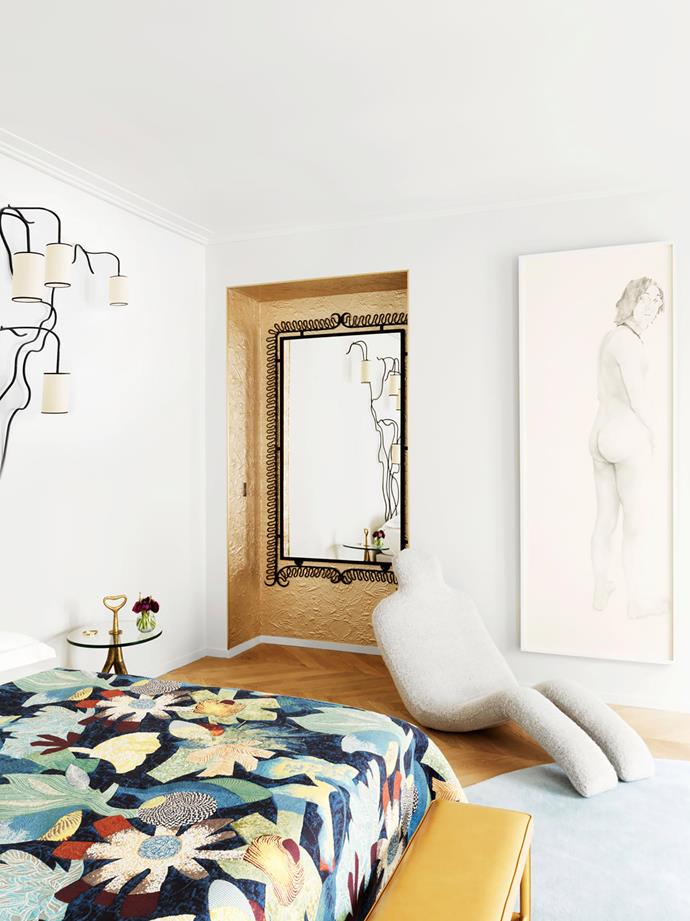 "The bedspread is made in Lelièvre 'Tropical Jungle' fabric. Vintage 'Liane' wall light by Jean Royère. Bedside table by Gio Ponti. Vintage 'Bouloum' chaise by Olivier Mourgue beside a life-size drawing of John Lennon, signed ""Angelini"". C1950s mirror in niche by the Ateliers Gouffé."