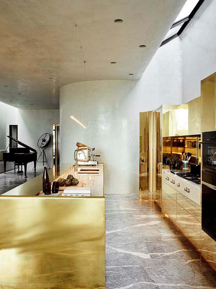 "Architect Rob Mills transformed this [former cardboard factory](https://www.homestolove.com.au/luxurious-transformation-of-a-former-factory-in-melbourne-6171|target=""_blank"") into a luxurious family home. The striking polished brass island bench in the kitchen stands out against the grey-veined marble."