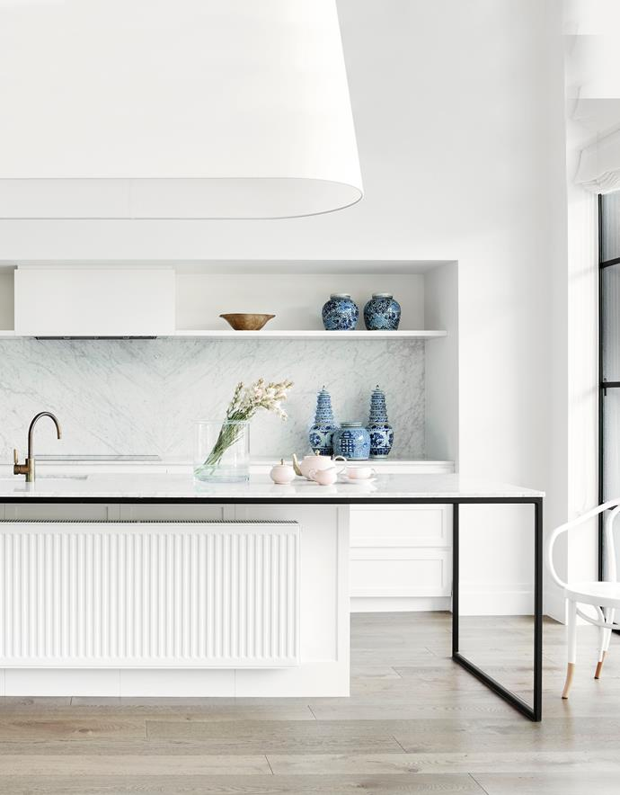 The black steel frame supporting the Carrara marble island bench captures the negative space below the bench in this Alexandra Brownlow-designed kitchen. It also cleverly allows a large DeLonghi hydronic heating panel from DPP Hydronic Heating to effectively heat the room and warm up the cold marble in winter.