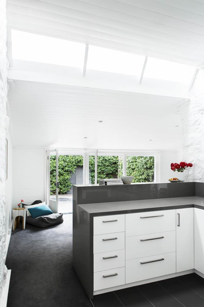 "Light pours through the glass skylights in this open-plan [kitchen and living area](https://www.homestolove.com.au/gallery-georgias-light-filled-melbourne-terrace-2242|target=""_blank"") designed by Georgia Hobart."