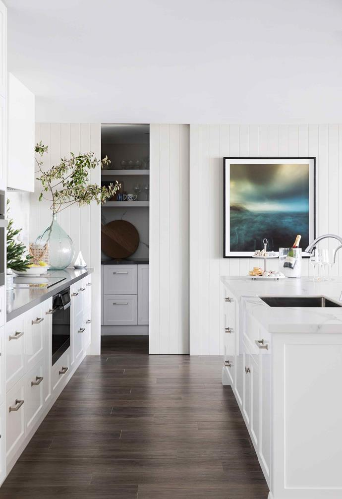 "A clever sliding door hides the butler's pantry from view when not in use in this [modern Hamptons-style home](https://www.homestolove.com.au/modern-hamptons-home-sydney-19531|target=""_blank""). The weatherboard panelling matches that of the internal wall cladding creating a seamless look."