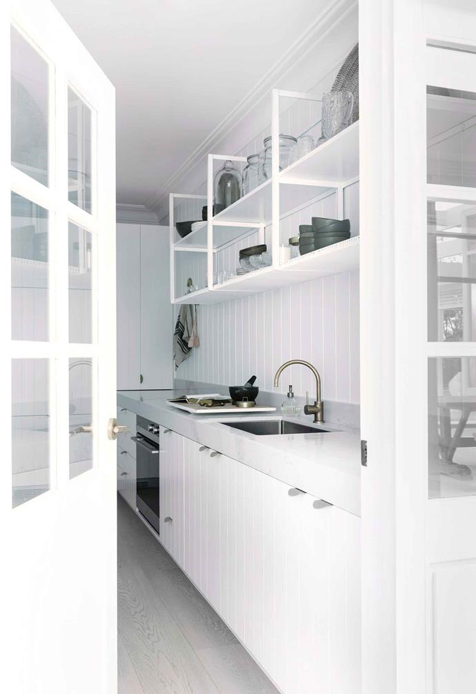 "Making a statement of her butler's pantry, [Three Birds Renovation's Bonnie Hindmarsh](https://www.homestolove.com.au/three-birds-bonnie-hindmarshs-modern-coastal-home-6802|target=""_blank"") used white doors with glass panels to connect the space with the rest of the home. Open gantry-style shelving above pairs beautifully with white weatherboards and cabinetry."