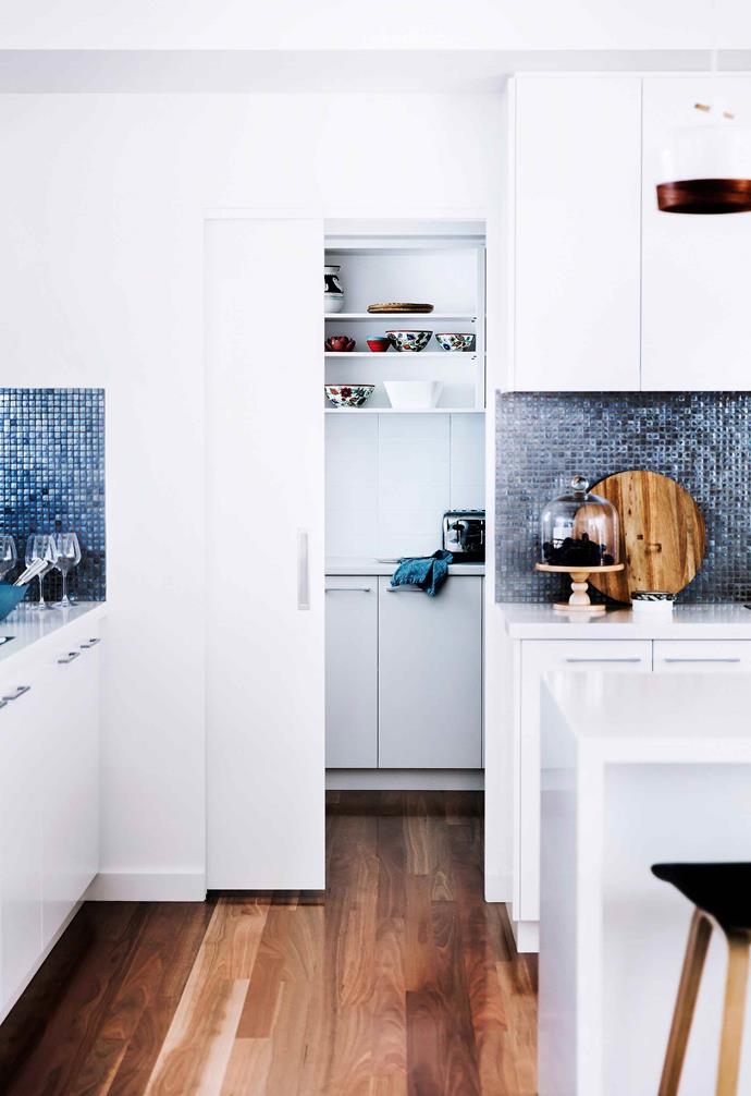 In the main kitchen of this home a stunning blue mosaic tile forms the splashback, creating a glittering effect. Tucked behind a sliding cavity door the butler's pantry is all business with ample prep space and storage.