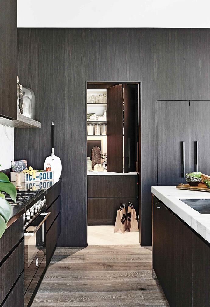 Tucked to the side, the butler's pantry in this Melbourne home features a mirrored splashback that amplifies the light within the room. A bi-fold cabinet front hides shelving at will.
