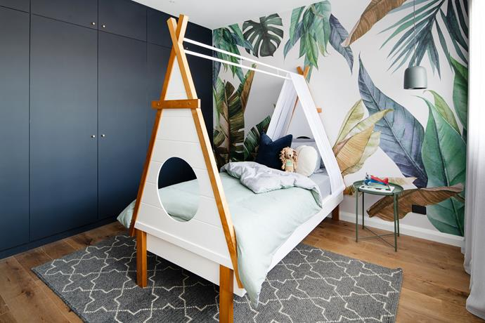 "This jungle-themed kids bedroom, featuring statement botanical wallpaper and a teepee-inspired bed from [Amart Furniture](https://www.amartfurniture.com.au/hopi-58356/|target=""_blank""