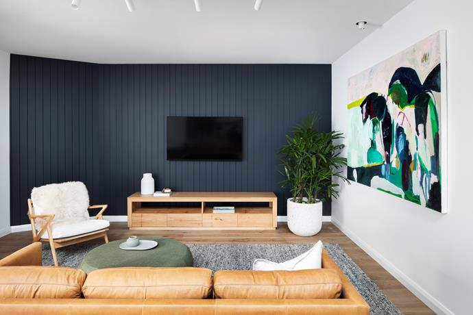 A dark feature wall adds drama and depth to the living room, allowing the colourful artwork, light timber furniture and leather lounge to pop.