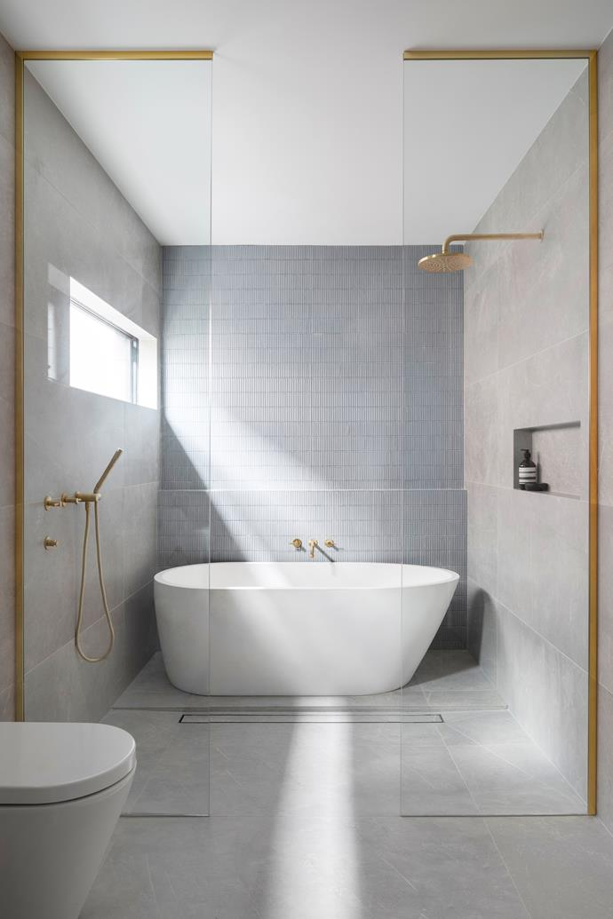 "Timeless finishes and a functional layout mean the bathroom is luxurious but still user-friendly. ""The large-format tiles look really grand and are easy to maintain,"" Bec says. ""It feels warm, inviting, spacious and comfortable."" A freestanding bath from [Concrete Nation](https://www.concretenation.com.au/