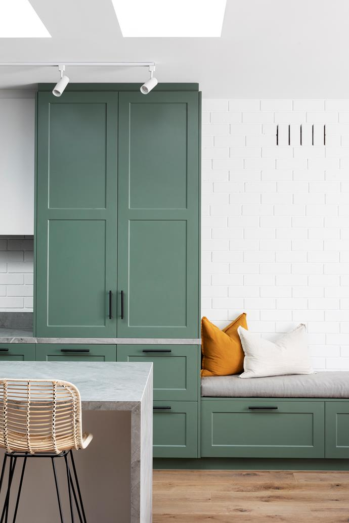Sage green cabinets painted in Dulux 'Spiralina' and white-painted brick walls create a fresh yet welcoming feel in the kitchen.