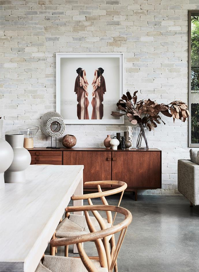 An exposed brick feature wall in the home's dining area was made from salvaged materials. A photographic artwork by Murray Hilton hangs above the vintage Danish sideboard.