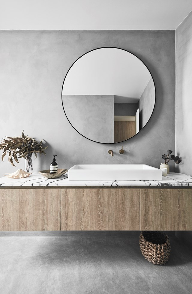 This serene bathroom features polished concrete tiles, timber-look cabinetry and a New York marble vanity top to mirror the materials used in the kitchen. The muted tones and natural finishes give the space an organic feel.