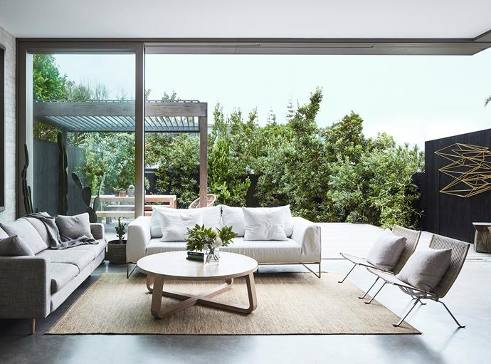 "A light-filled living space opens up to the outdoor area. ""It's the perfect place for gatherings,"" Aaron says. The indoor sofas are from Project 82 and MCM House, with Fritz Hansen 'PK22' armchairs providing extra seating, while a round Zuster coffee table sits atop the Armadillo&Co rug."