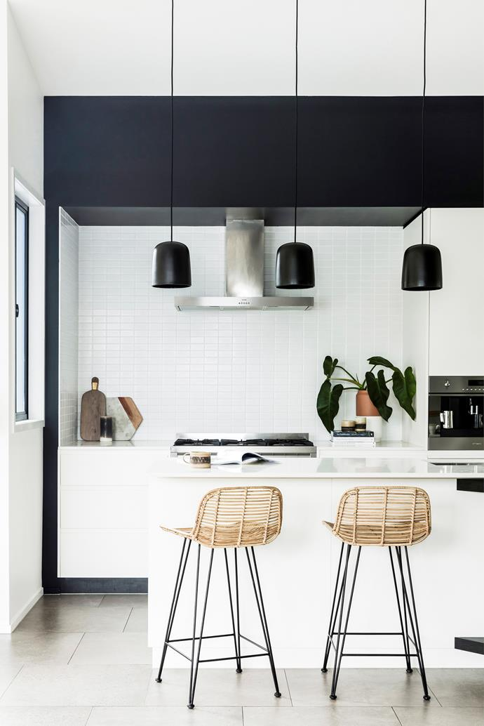 The kitchen is a study in contrast, with the white cabinetry, benches and splashback juxtaposed against the black bulkhead and trio of pendants. Terracotta planters, earthen ceramics and woven bar stools help to add warmth and texture.