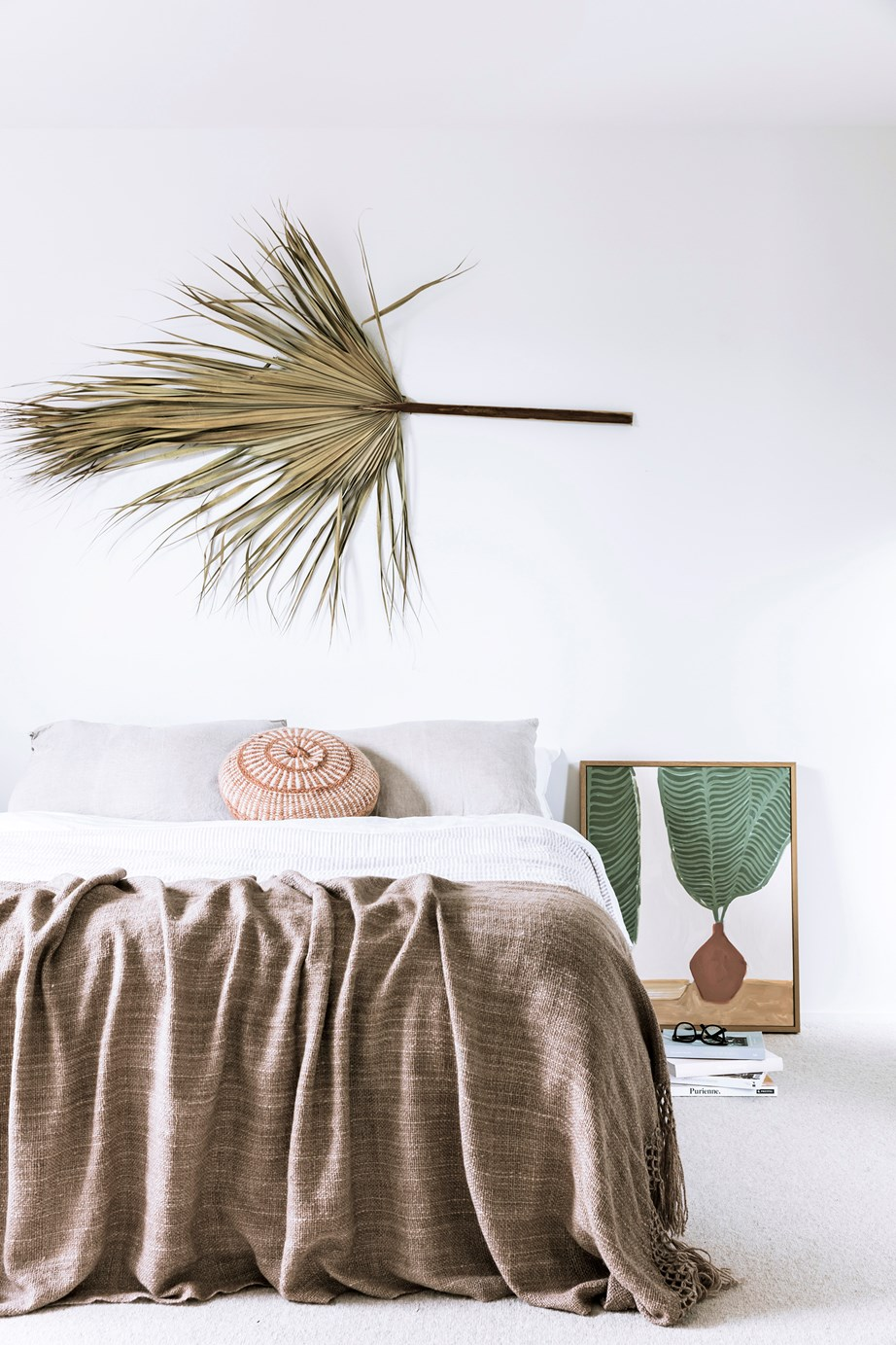 In a nod to the home's coastal location, the couple's bedroom features textural woven bedding, a tropical-themed artwork and a dried palm frond-turned-wall feature.
